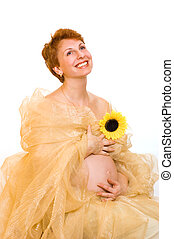 Beautiful pregnant woman with a sunflower