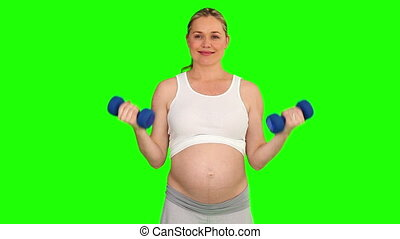 Beautiful pregnant woman with dumbbells