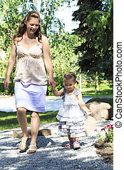 Beautiful pregnant woman with her ??little daughter walking