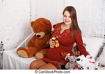 Beautiful pregnant woman with soft toys