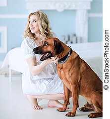 pregnant young woman with her pet sitting on bed in bedroom