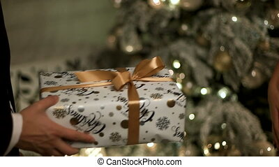 Beautiful present in a white and gold colored box made by a man in a classical suit for his girlfriend.