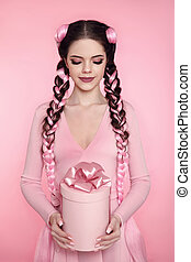 Beautiful pretty teen girl present gift box with bow over pink studio background. Attractive brunette with braided hair.
