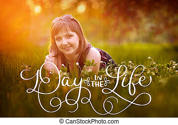 Beautiful pretty woman lying on the grass in the sun and text Day in the life. Calligraphy lettering vintage hand draw