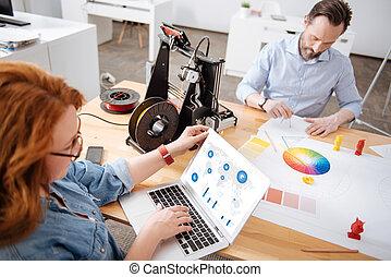 Beautiful professional designer looking at the statistics