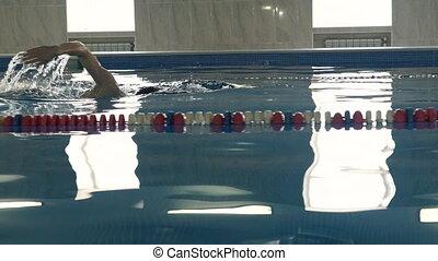 Beautiful professional swimmer swiming crawl stroke reaching...