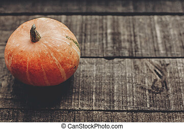 beautiful pumpkin on rustic wooden background, top view. space for text. halloween or thanksgiving concept greeting card. cozy autumn mood. fall holiday. stylish simple image