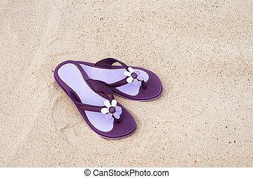 Beautiful purple flip-flops on the beach - Close-up of...