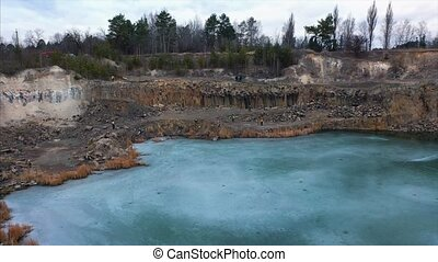 Beautiful quarry, the lake is covered with thin ice, air...