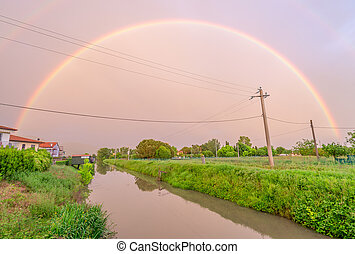 Beautiful rainbow at sunset over a small river in Tuscany, Italy