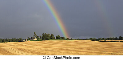 Beautiful rainbow in dark sky over field the harvest of wheat.