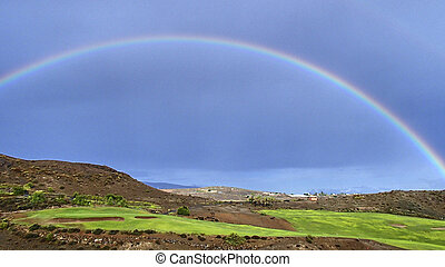 Beautiful rainbow in the blue sky over a golf course