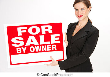Beautiful Realtor holds a for sale sign