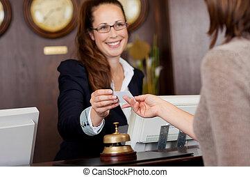 Beautiful receptionist handing over a card - Beautiful...