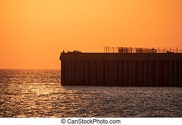Beautiful red and orange sunset over the sea. Silhouette of a pier with fishermen at sunset