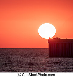 Beautiful red and orange sunset over the sea. The sun goes down over the sea. Silhouette of a pier with fishermen at sunset