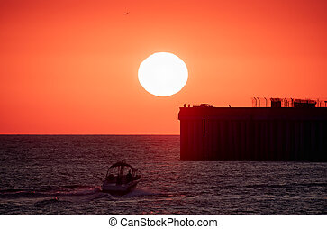 Beautiful red and orange sunset over the sea. The sun goes down over the sea. Silhouette of a pier with fishermen and boat at sunset