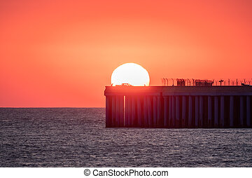 Beautiful red and orange sunset over the sea. The sun goes down over the sea. Silhouette of a pier with people at sunrise