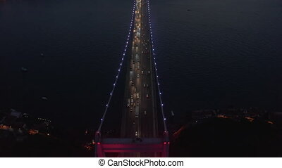 Beautiful Red Bridge over Bosphorus in Red light at Night with Car Traffic, Aerial Birds Eye View tilt down
