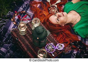 Beautiful red hair woman lying in grass