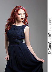 Beautiful red-haired fashion model posing in evening dress and in the diadem over dark background. Wavy Red Hair. Fashion Girl Portrait.