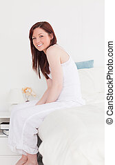 Beautiful red-haired female posing while sitting on her bed
