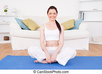 Beautiful red-haired female stretching in the living room