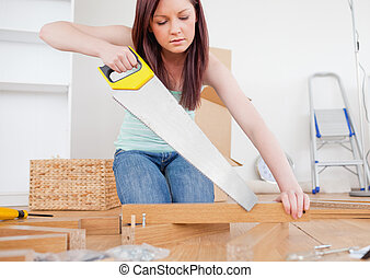Beautiful red-haired female using a saw for diy at home
