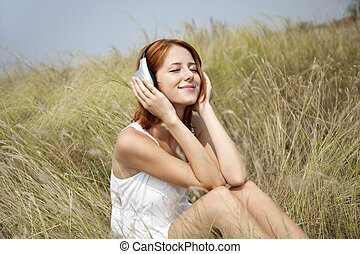 Beautiful red-haired girl at grass with headphones