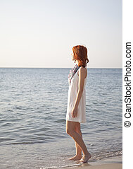 Beautiful red-haired girl at sunrise on the beach.