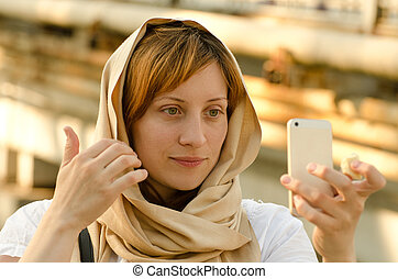 Beautiful red-haired girl in a scarf looks in a smartphone