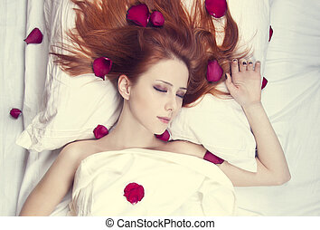Beautiful red-haired girl in bed with rose petal. Studio shot.