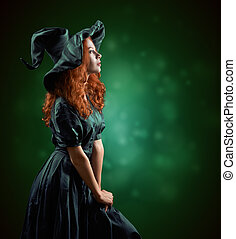 beautiful red-haired girl in green costumes witch blurred background