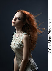 beautiful red-haired girl in the dark blue background