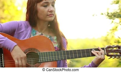 Beautiful red-haired girl playing guitar