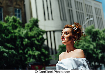 beautiful red-haired girl standing on the street