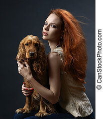 beautiful red-haired girl with a dog in the dark