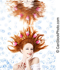 Beautiful red-haired girl with tulips in hair underwater. Art photo.