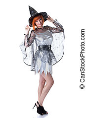 Beautiful red-haired model posing in witch costume