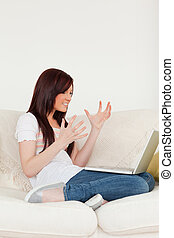Beautiful red-haired woman being depressed after gambling with her laptop while sitting on a sofa in the living room