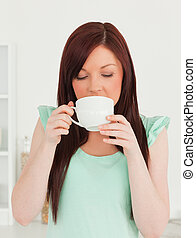 Beautiful red-haired woman having her breakfast in the kitchen