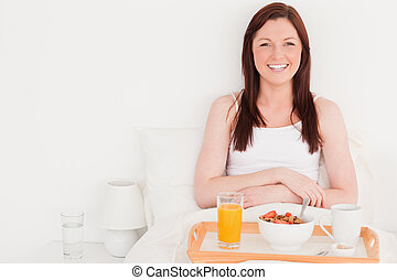 Beautiful red-haired woman having her breakfast