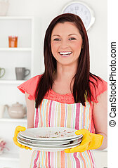 Beautiful red-haired woman holding some dirty plates