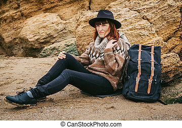 Beautiful red-haired woman in a hat and a scarf with a backpack sits on the coast on the background of the rocks. Tourism, rest, lifestyle.