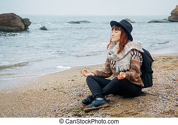 Beautiful red-haired woman in a hat and scarf with a backpack sits in a meditative position on the coast against the background of the rocks against the beautiful sea. Tourism, rest, lifestyle.