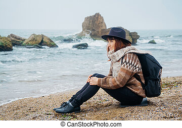 Beautiful red-haired woman in a hat and scarf with a backpack sits on the coast against the background of the rocks against the beautiful sea. Tourism, rest, lifestyle.