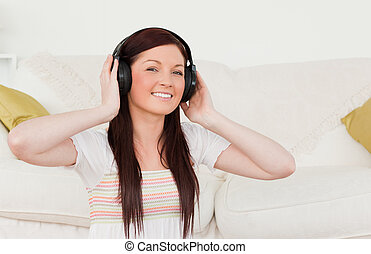 Beautiful red-haired woman listening to music with headphones while sitting on a carpet in the living room