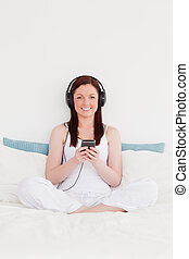 Beautiful red-haired woman listening to music with her headphones while sitting on her bed