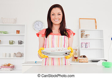 Beautiful red-haired woman posing while holding some dirty plates in the kitchen in her appartment