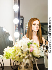 beautiful red-haired woman sitting in front of a mirror